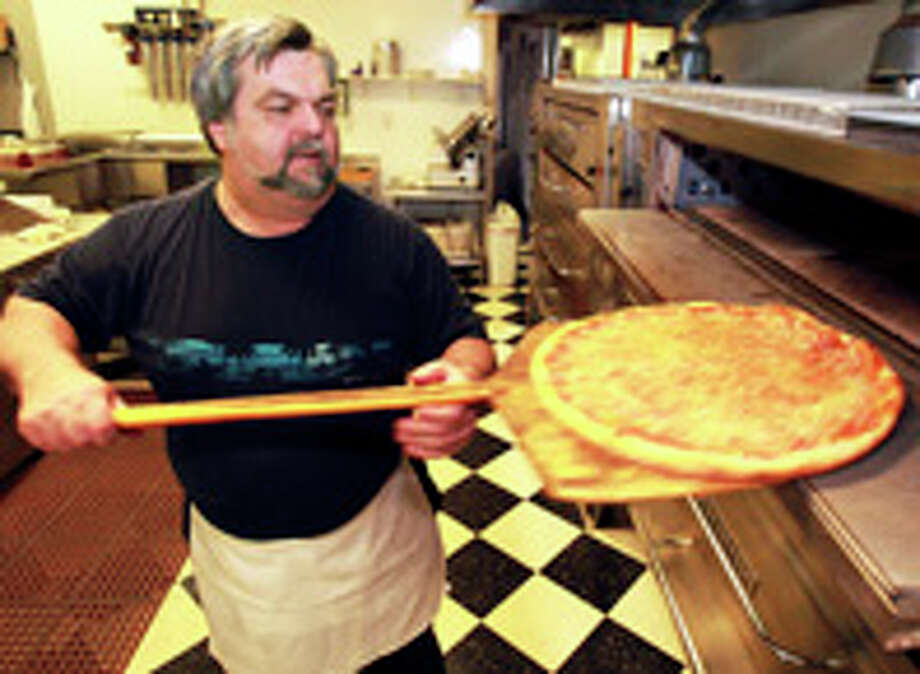 Steve Florio at Florio's Pizza removes a pizza from the oven. / © 2011 San Antonio Express-News