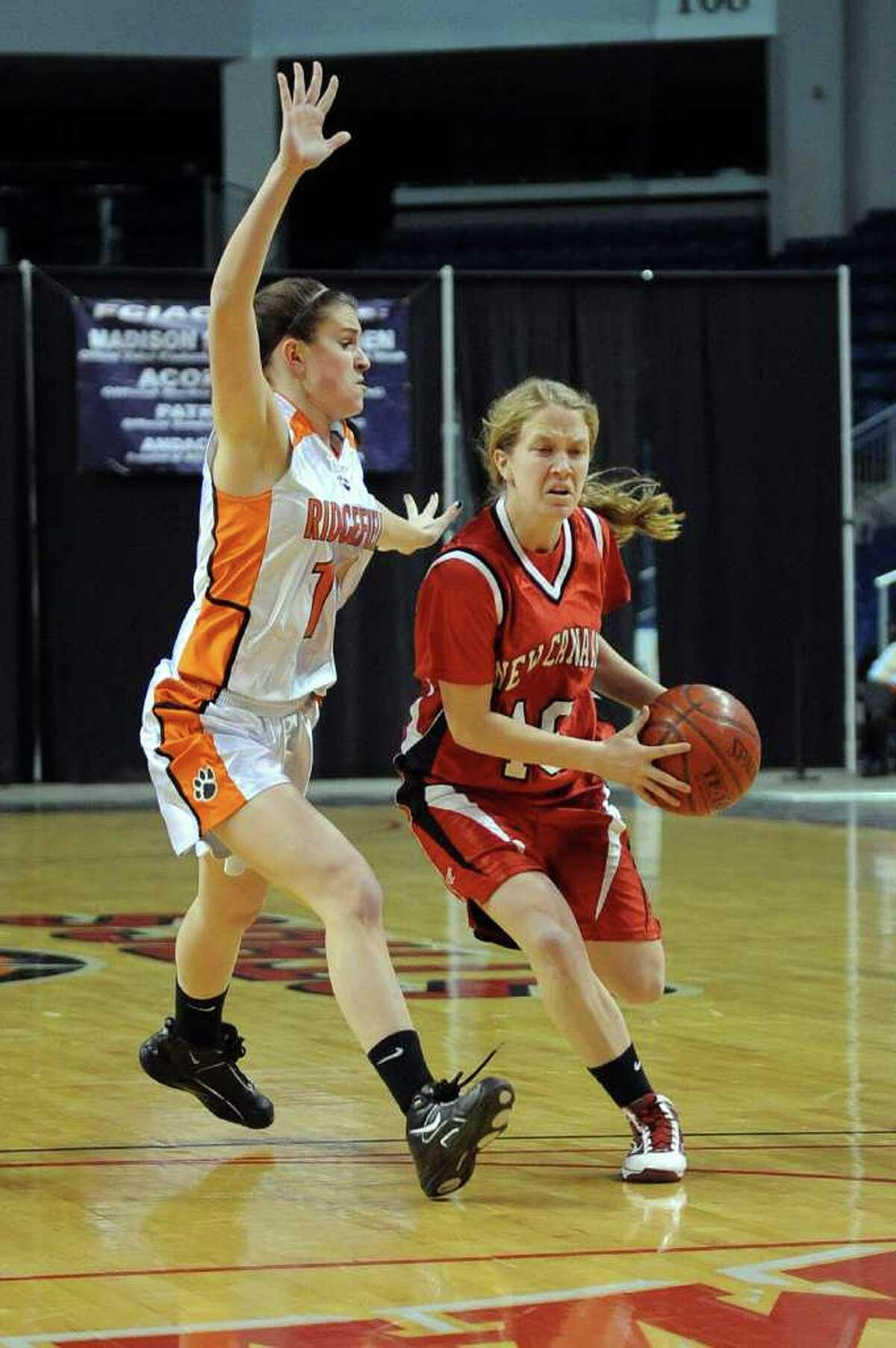 New Canaan's Sara Mannelly dribbles past Ridgefield's Kathryn Cholko during Tuesday's FCIAC girls basketball semifinal game at the Webster Bank Arena at Harbor Yard on Feburary 22, 2011.