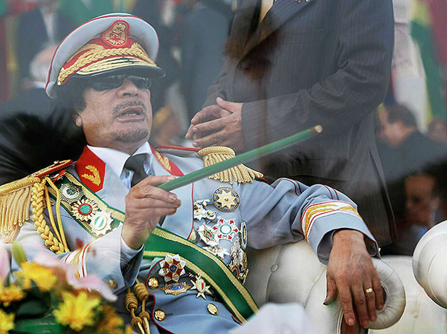 Libyan leader Moammar Gadhafi gestures with a green cane as he takes his seat behind bulletproof glass for a military parade in Green Square, Tripoli, Libya. Photo: Ben Curtis, ASSOCIATED PRESS / AP