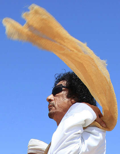 Libyan leader Moammar Gadhafi adjusts his scarf as he receives Omani's Sultan Qaboos bin Said, not p