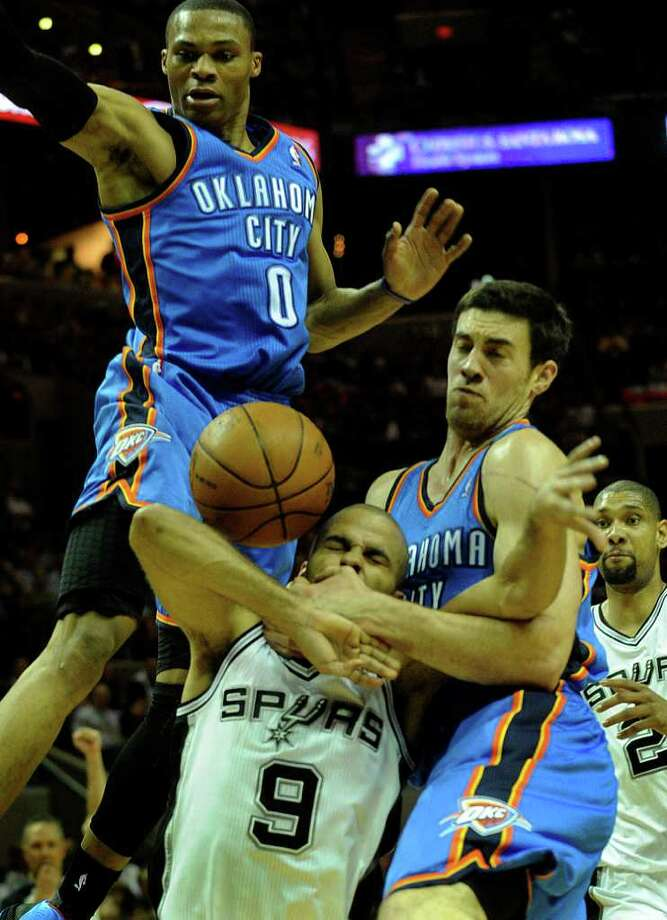 Tony Parker (9) of the San Antonio Spurs is fouled hard by Nick Collison, right, of the Oklahoma City Thunder as Russell Westbrook (0) defends during first-half NBA action at the AT&T Center on Wednesday, Feb. 23, 2011. A shoving match ensued after the play, with technical fouls being called. BILLY CALZADA / gcalzada@express-news.net