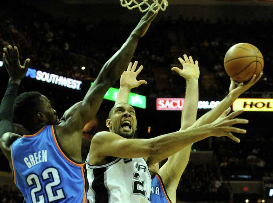 Tim Duncan of the San Antonio Spurs shoots between Jeff Green, left, and Nick Collison of the Oklahoma City Thunder during first-half NBA action at the AT&T Center on Wednesday, Feb. 23, 2011. BILLY CALZADA / gcalzada@express-news.net