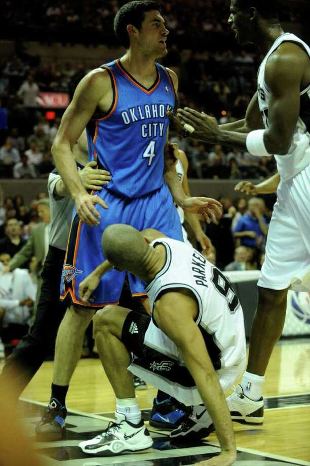 Nick Collison of the Oklahoma City Thunder (4) is held back by an official after he committed a hard foul on Tony Parker (9) of the San Antonio Spurs during first-half NBA action at the AT&T Center on Wednesday, Feb. 23, 2011. Antonio McDyess of the Spurs, right, approaches Collison. BILLY CALZADA / gcalzada@express-news.net