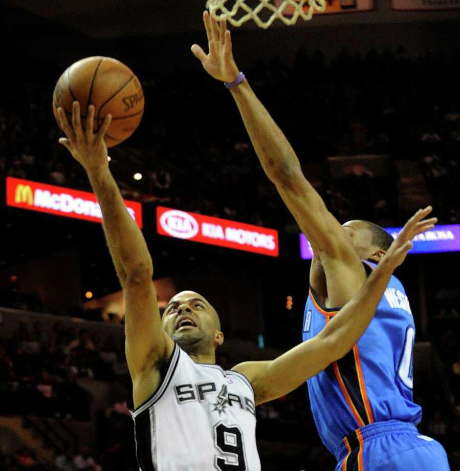 Tony Parker of the San Antonio Spurs (9) drives past Russell Westbrook of the Oklahoma City Thunder to score during first-half NBA action at the AT&T Center on Wednesday, Feb. 23, 2011. BILLY CALZADA / gcalzada@express-news.net