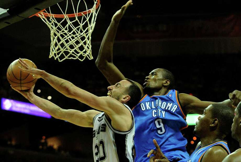 Manu Ginobili of the Spurs shoots against Serge Ibaka of the Oklahoma City Thunder during second-half NBA action at the AT&T Center on Wednesday, Feb. 23, 2011. BILLY CALZADA / gcalzada@express-news.net