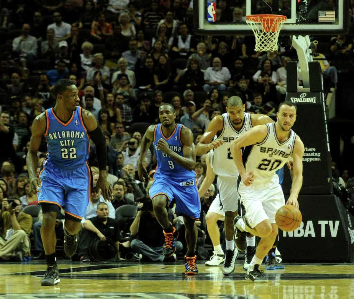 Manu Ginobili of the San Antonio Spurs (20) brings the ball down the court as teammate Tim Duncan and Jeff Green (22) and Serge Ibaka (9) of the Oklahoma City Thunder give chase during second-half NBA action at the AT&T Center on Wednesday, Feb. 23, 2011. BILLY CALZADA / gcalzada@express-news.net Oklahoma City Thunder at San Antonio Spurs