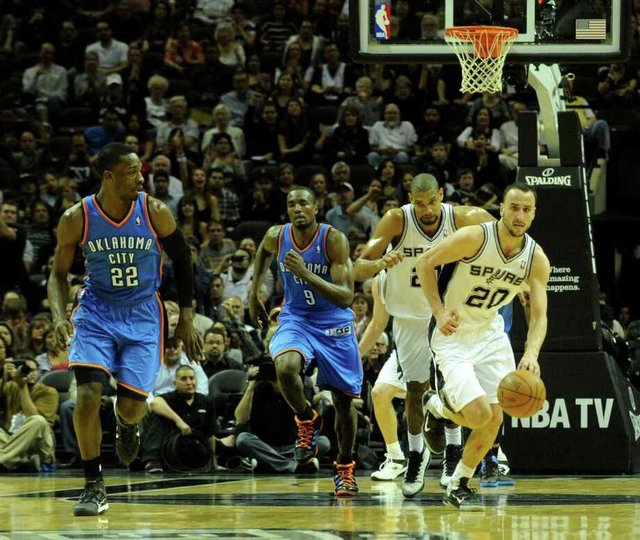 Manu Ginobili of the San Antonio Spurs (20) brings the ball down the court as teammate Tim Duncan and Jeff Green (22) and Serge Ibaka (9) of the Oklahoma City Thunder give chase during second-half NBA action at the AT&T Center on Wednesday, Feb. 23, 2011. BILLY CALZADA / gcalzada@express-news.net