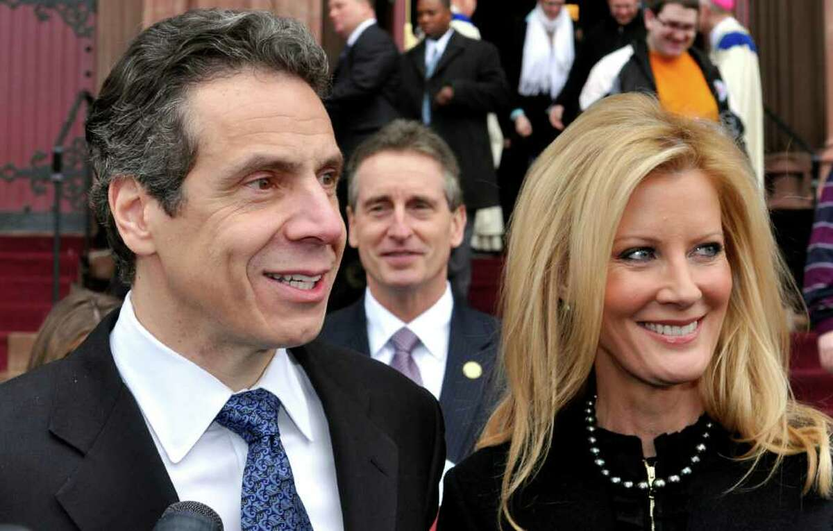 FILE - This Jan. 2, 2011 file photo shows New York Gov. Andrew Cuomo, left, with his girlfriend, Sandra Lee, and Lt. Gov. Robert Duffy, center, in front of the Cathedral of the Immaculate Conception, in Albany, N.Y., after attending Sunday services. The father, the son and the question of whether to grant communion to Catholics who openly flout canon law has once again reared up in New York where a Vatican consultant is calling to deny the host to Gov. Cuomo while he is living with his girlfriend. More than 25 years ago, Cuomo's father, Gov. Mario Cuomo, ran afoul of the church for his support of abortion rights. (AP Photo/Stewart Cairns, File)
