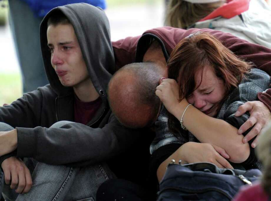 Fifteen-year-old Kent Manning, left, and his sister Libby, 18, react with their father, who asked not to identified, after they were told by police that there was no hope of finding Kent and Libby's mother alive in a collapsed building following a 6.3-magnitude earthquake Tuesday,  in Christchurch, New Zealand, Wednesday, Feb. 23, 2011.  (AP Photo/Rob Griffith) Photo: Rob Griffith