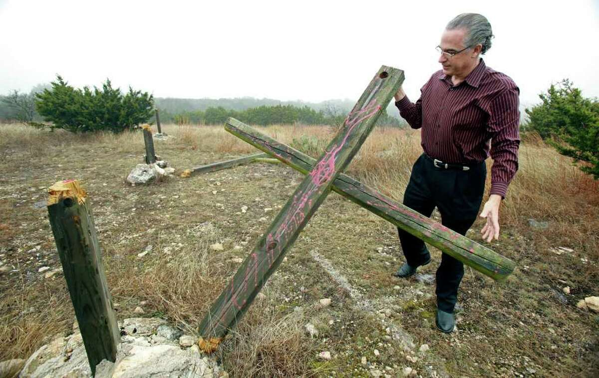 """Jay Parker hoists a defaced cross that had been hacked down. Juveniles are suspected of the criminal mischief, which some are calling """"satanic ritual."""""""