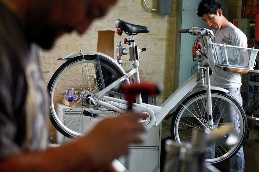 Fernando Guajardo (left), service manager at Bike World on Broadway, and Zack Gonzales, a mechanic at Bike World, work to assemble 140 bikes to be used for San Antonio's new B-cycle bike sharing program at the main office for the program in HemisFair Park on Wednesday, Feb. 23, 2011.