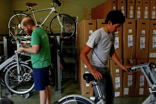 Caleb Choate (left) and Zack Gonzales, both mechanics at Bike World, work to assemble 140 bikes to be used for San Antonio's new B-cycle bike sharing program at the main office for the program in HemisFair Park on Wednesday, Feb. 23, 2011. Photo: LISA KRANTZ, Lisa Krantz/Express-News / SAN ANTONIO EXPRESS-NEWS