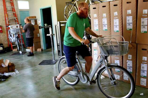 Caleb Choate, a mechanic at Bike World, rides a bike he just assembled outside to its parking spot as he works with others to assemble 140 bikes to be used for San Antonio's new B-cycle bike sharing program at the main office for the program in HemisFair Park on Wednesday, Feb. 23, 2011. Photo: LISA KRANTZ, Lisa Krantz/Express-News / SAN ANTONIO EXPRESS-NEWS