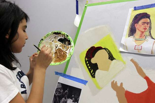Izzy Castro, 11, paints details on Frida Kahlo's face as participants put the final touches on the murals, February 19, 2011. Girls Inc. of San Antonio and SAY Si partnered to create a mobile mural called Herstory. The six-panel mural immortalizes women trailblazers and activists who paved the path for women today, including Sandra Cisneros, Maria Antonietta Berriozabal, Ann Richards and Emma Tenayuca. The mural will be unveiled Feb. 26. Photo: JENNIFER WHITNEY, Special To The Express-News / special to the Express-News