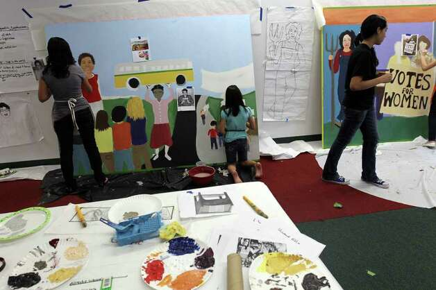 Participants put the final touches on the murals, February 19, 2011. Girls Inc. of San Antonio and SAY Si partnered to create a mobile mural called Herstory. The six-panel mural immortalizes women trailblazers and activists who paved the path for women today, including Sandra Cisneros, Maria Antonietta Berriozabal, Ann Richards and Emma Tenayuca. The mural will be unveiled Feb. 26. Photo: JENNIFER WHITNEY, Special To The Express-News / special to the Express-News