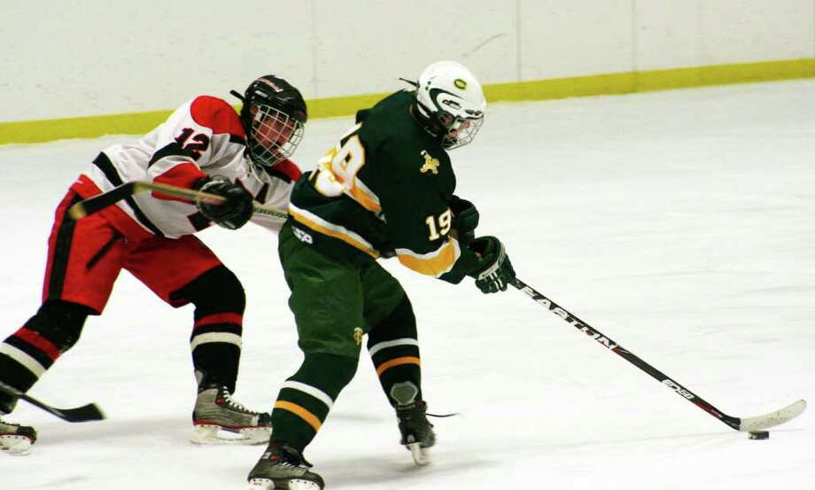 Fairfield hockey's Graeme Keleher defends Trinity Catholic's Stephan Klosz during the Mustangs' 5-4 loss to the Crusaders on Wednesday night at Wonderland of Ice. Photo: Tim Parry / Fairfield Citizen freelance