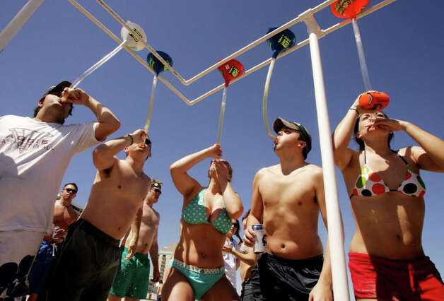 Students from Texas A&M and The University of Texas at Austin use beer bongs to drink a whole can of beer at one time on the beach at South Padre Island Saturday afternoon, March 8, 2008.  The weekend marks the beginning of Texas Week, the busiest week of the spring break season for the island.  (AP Photo/The Monitor, Kirsten Luce)  ** MAGS OUT, NO SALES, INTERNET: AP MEMBERS ONLY  ** Photo: Kirsten Luce, AP / The Monitor