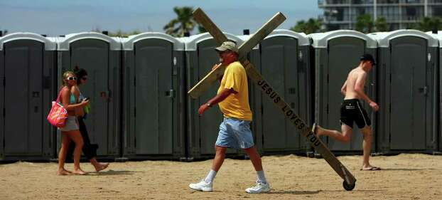 Larry Gross of Utopia, Texas walks down the beach on South Padre Island during Spring Break 2007. Gross started walking with the giant cross all over Texas in 1987 when he beat his heroine addiction and found Jesus. JOHN DAVENPORT / STAFF Photo: JOHN DAVENPORT, SAN ANTONIO EXPRESS-NEWS / SAN ANTONIO EXPRESS-NEWS