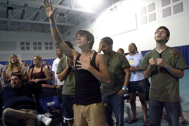Zach Almond (front, center, arm raised) prays with other participants involved with Beach Reach at the convention center on South Padre Island during Spring Break 2007. Most of those involved in the faith based effort are Baptist college students and come down to the island to encourage other partying students to accept Christ into their lives. JOHN DAVENPORT / STAFF Photo: JOHN DAVENPORT, SAN ANTONIO EXPRESS-NEWS / SAN ANTONIO EXPRESS-NEWS