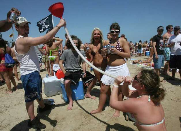 Holly Kaufhold (bottom, right) drinks beer from a beer bong at South Padre Island, Texas on Tuesday March 13, 2007. The revelry took place as members of Beach Reach built a religious-theme sand sculpture nearby. JOHN DAVENPORT / STAFF Photo: JOHN DAVENPORT, SAN ANTONIO EXPRESS-NEWS / SAN ANTONIO EXPRESS-NEWS