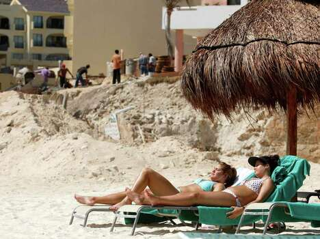 Caroline Keener, of Dallas, Texas, right, and Ally Wade, of San Antonio, Texas, take in the sun as construction workers continue renovations on a hotel, Tuesday, March 14, 2006, in Cancun, Mexico. As Cancun looks to renew itself from its spring break roots and from the destruction left from last year's hurricane season, hotels like Le Blanc have moved in to provide more upscale, serene accomodations. Photo: GREGORY BULL, AP / AP