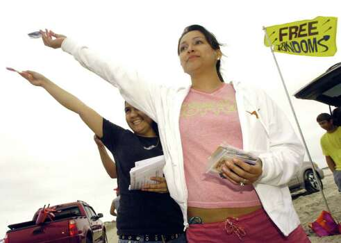 Melissa Rios, volunteer from Planned Parenthood of South Texas Male Central Clinic, left, and Teresa Arredondo, community educator for the clinic, pass out free condoms to spring breakers at J.P. Luby Surf Park Beach in Corpus Christi, Texas Wednesday, March 15, 2006. Employees and volunteers have passed out condoms since Monday, March 13, 2006, and will be out at the beach until Saturday passing out condoms and educational information. Photo: TODD YATES, AP / CORPUS CHRISTI CALLER-TIMES