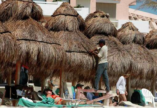 Tourists sit in the sun as restoration work continues on an adjacent palapa in Cancun, Mexico, Tuesday, March 14, 2006. The sugar-white sand beaches are back after being swept away by Hurricane Wilma five months ago. But there are no stages for wet T-shirt contests, and MTV won't be hosting its spring break beach party. Instead, the first wave of winter-weary college students who converged on Cancun found that construction workers nearly outnumbered revelers this week in Mexico's spring break capital of beer and bikinis. Photo: GREGORY BULL, AP / AP