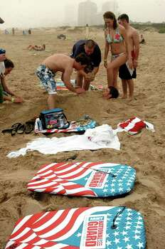 STATE/DAILY/ SPRING BREAL 2006: Rusty Blum,21 of the University of Iowa gets buried in the sand by his fellow classmates while on the beach at South Padre Monday March 13, 2006. DELCIA LOPEZ/STAFF Photo: DELCIA LOPEZ, SAN ANTONIO EXPRESS NEWS / SAN ANTONIO EXPRESS NEWS