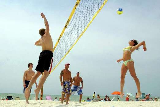 Megan Valicevic, of Texas, right, hits a shot as Jason Barvels of Minnesotta, front left, tries to block it, during a pick-up game of beach volleyball at Bonita Beach in Bonita Springs, Fla., Monday, March 21, 2005. Other players are, from back left to right, Andy Secor, of Minnesotta, Cary Coburn, of Bonita Springs, and Dave Kinst, also of Bonita Springs. Photo: DARRON R. SILVA, AP / NAPLES DAILY NEWS