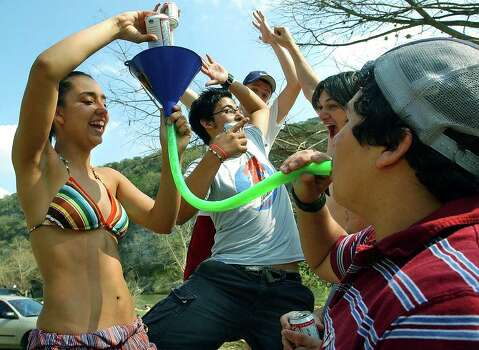"METRO  Vanessa Silva (left) pours beer into the funnel end of a ""beer bong"" as Joe Anthony guzzles the cold liquid with spring break party friends cheering him on Tuesday, March 16, 2004 on the Guadalupe River.    BEER BONGS ON THE GUADALUPE RIVER  MARCH 16, 2004    TOM REEL/STAFF Photo: TOM REEL, SAN ANTONIO EXPRESS-NEWS / SAN ANTONIO EXPRESS-NEWS"