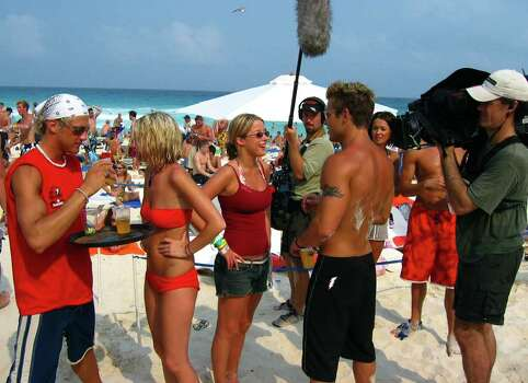"**ADVANCE FOR WEEKEND EDITIONS, APRIL 3-6** Crew members of the spring break reality movie are filmed as they enjoy themselves on Cancun beach, March 20, 2003, in Mexico. With dozens of wildly popular reality shows crowding the television airwaves, it was only a matter of time before Hollywood took a crack at its own version of ""real life."" The two-producer team that created MTV's ""The Real World"" has taken the phenomenon south of the border, throwing 16 college students together in a hotel and taping every minute of the spring break insanity that follows. Photo: JOSE LUIS MAGANA, AP / AP"
