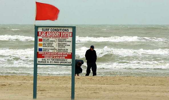 STATE/DAILY/ Spring Break 2003: Two brave beach combers search for shells along the jetties beach side at South Padre Island March 6, 2003. Cold high winds and rainy weather brought out the red warning flag for heavy surf and danergous currents. Many spring-breakers found themselves staying in. DELCIA LOPEZ/STAFF Photo: DELCIA LOPEZ, SAN ANTONIO EXPRESS NEWS / SAN ANTONIO EXPRESS NEWS