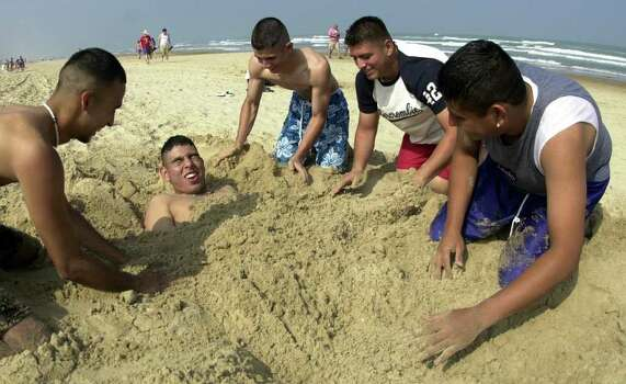 University of Texas - El Paso students, from left, Tony Gonzalez, Albert Portales, Ruben Gonzales and Hector Llanas bury their friend Alex Moreno from Houston in the sand during their week of fun at Spring Break on South Padre Island, Texas, Thursday, March 14, 2002. Photo: JAMES NEDOCK, AP / THE MONITOR