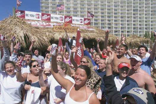 Crowds show their preference for softdrink, as they hold up Dr. Pepper cans at one of many marketing booths during Spring Break in Panama City Beach, Fla., on Friday, March 22, 2002.  Drugs, alcohol and crowd mentality all make spring break a dangerous time.  For six weeks every year, the Bay Medical Center in nearby Panama City,  gears up as hundreds of thousands of students flock to nearby Panama City Beach, the nation's leading spring break destination. Photo: DANA MISEREZ, AP / PANAMA CITY NEWS HERALD