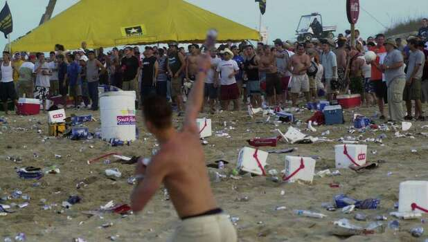 A man lobs a beer can Thursday, March 14, 2002, on South Padre Island, Texas, during a melee that broke out during parties by spring break participants. The crowd broke into groups and threw cans and bottles for about half an hour. Random fist fights broke out. South Padre Island officials said the incident was commonplace for a spring break crowd. Sgt. Ed Pace said police did nothing to subdue the crowd because the incident wasn't serious enough. Photo: JAMES NEDOCK, AP / THE MONITOR