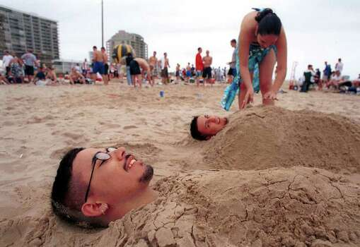 "Alfonso Mendez, an ITT student from San Antonio, enjoys being buried in the sand during Spring Break on South Padre Island, Texas, on Saturday March 10, 2001. At right, Mendez's sister, Cristina Mendez, a Junior at Brackenridge High School buries friend Christopher Ramirez who is also from San Antonio. Saturday marked the kick off of ""Texas Week,"" in the beach destination with the larger universities and many high schools beginning their week long vacation today.  SPECIAL TO EXPRESS-NEWS/Photo by Alicia J. Wagner Photo: Alicia J. Wagner, Freelance"
