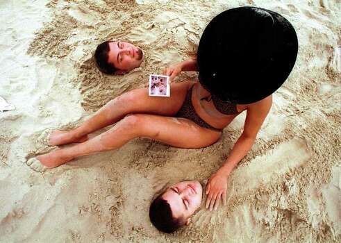 "Lisa Pina, a junior at St. Thomas in Houston, buries her two friends in the sand and looks at a polaroid of them. Above is Jonathan Martello, a junior at San Jacinto College and at below is Justin Graves a University of Houston junior on South Padre Island, Texas, Saturday March 10, 2001. Saturday marked the beginning of ""Texas Week,"" during which most of the large Texas Schools are off for Spring Break.   SPECIAL TO EXPRESS-NEWS  Photo by Alicia J. Wagner Photo: Alicia J. Wagner, Freelance"