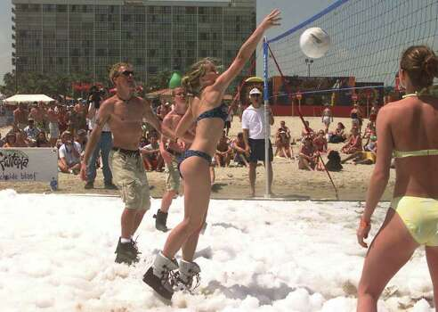 FOR IMMEDIATE RELEASE--FILE--Kara Miller hits a volleyball while playing on a special snow court made by an ice machine during spring break on South Padre Island, Texas, in this March 23, 2000, file photo. Players wore ice boots so they could stand on the snowy floor. South Padre Island continues to be a popular spring break destination for college students. Before last March gave way to April, 185,000 college kids had sunned, writhed and imbibed on Padre Island's shores. Photo: JOE HERMOSA, AP / THE BROWNSVILLE HERALD