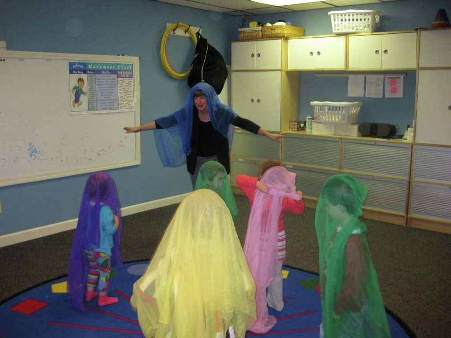 """Leslie Waddell, Kindermusik teacher, works with children during a """"Music for Little Hands"""" class. She and the kids are pretending it is raining, and the scarves are make-believe rain hats. Photo: Contributed Photo / Fairfield Citizen contributed"""