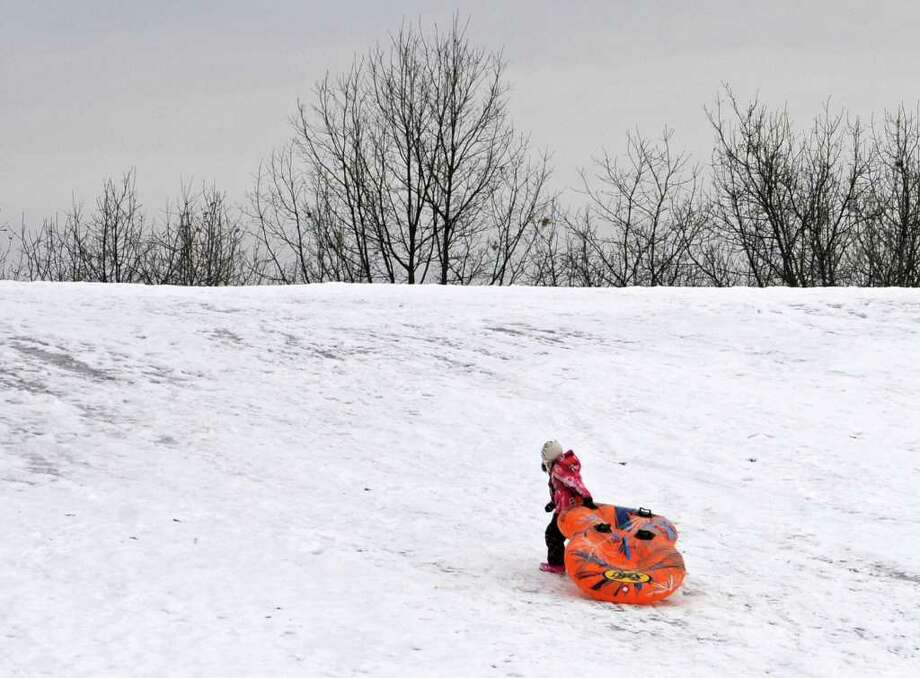A girl walks up a hill with her sled at Frear Park in Troy on Thursday. Friday promises to be harsher. National Weather Service meteorologists say snow will begin to move into the area between 4 and 7 a.m., with chances of sleet and rain increasing in areas west of Albany and southern Saratoga County. (Lori Van Buren / Times Union) Photo: Lori Van Buren