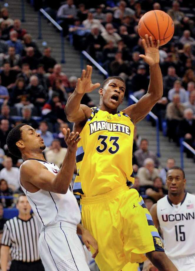 Marquette's Jimmy Butler, right, is fouled by Connecticut's Jamal Coombs-McDaniel during the first half of an NCAA college basketball game in Hartford, Conn., on Thursday, Feb. 24, 2011. (AP Photo/Fred Beckham) Photo: Fred Beckham, ASSOCIATED PRESS / Associated Press