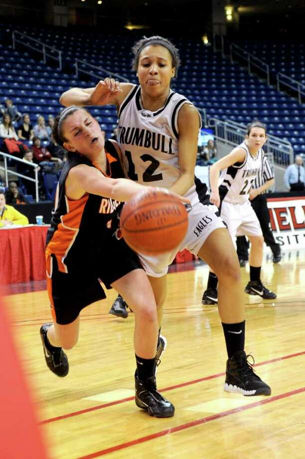 Trumbull's Taisha Lima and Ridgefield's Kathryn Cholko reach for the ball during Thursday's FCIAC girls basketball championship game at Webster Bank Arena at Harbor Yard on February 24, 2011. Photo: Lindsay Niegelberg / Connecticut Post