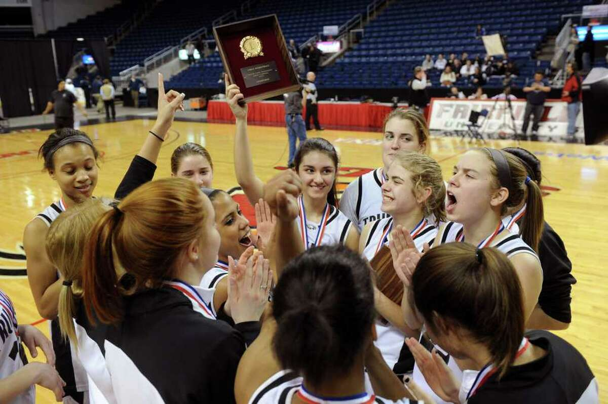 The Trumbull girls basketball team holds up their trophy after winning Thursday's FCIAC girls basketball championship game at Webster Bank Arena at Harbor Yard on February 24, 2011.