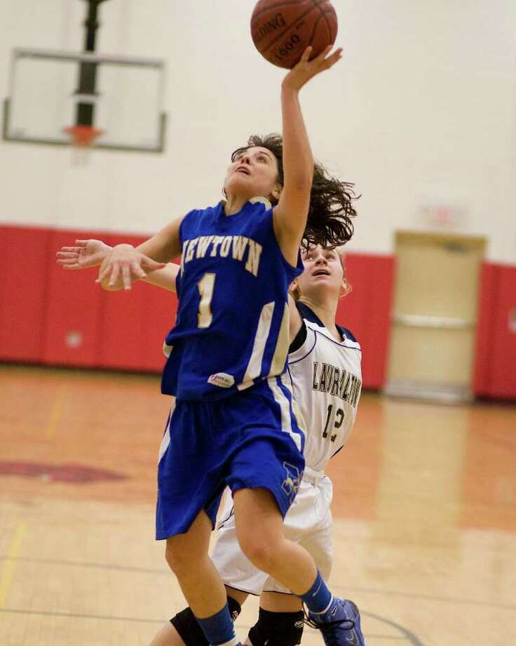 Newtown's Riley Wurtz drives by Lauralton Hall's Marisa Dowling for a layup during the SWC championship game Thursday night at Pomperaug High School. Photo: Barry Horn / The News-Times Freelance