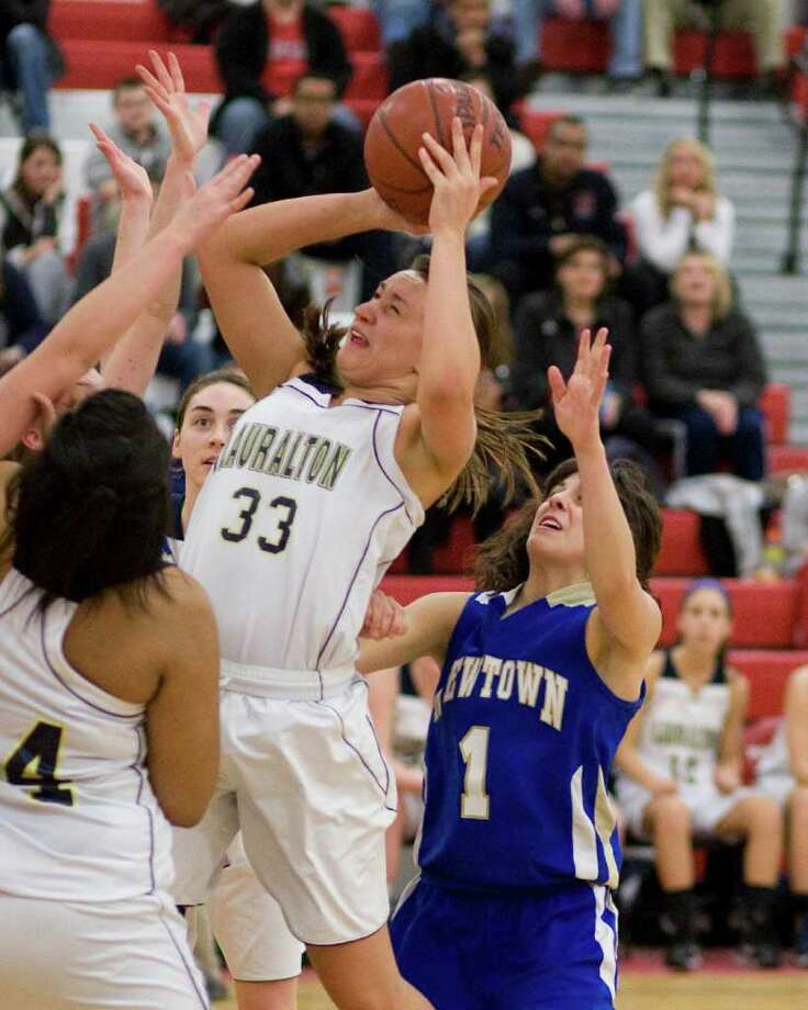 Lauralton Hall's Nicola Matero scores off an offensive rebound against Newtown in the SWC championship game Thursday night at Pomperaug High School. Photo: Barry Horn / The News-Times Freelance