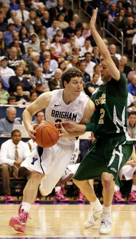 BYU's Jimmer Fredette, left, looks to pass the ball as Colorado State's Wes Elkmeier defends during the second half of an NCAA college basketball game in Provo, Utah, Wednesday, Feb. 23, 2011. BYU beat Colorado State 84-76. (AP Photo/George Frey) Photo: George Frey