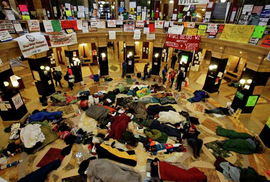 Opponents of the governor's bill to eliminate collective bargaining rights for many state workers sleep on the floor of the rotunda at the state Capitol in Madison, Wis., Thursday, Feb. 24, 2011, at the start of the tenth day of protests at the Capitol. (AP Photo/Andy Manis) Photo: Andy Manis