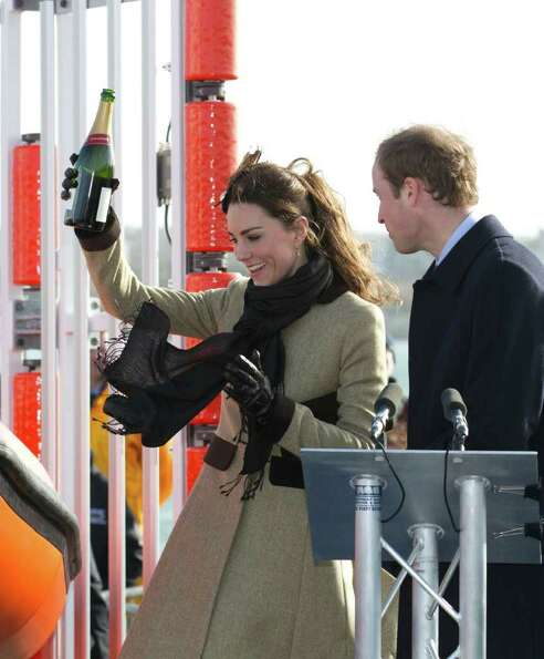 Britain's Prince William, right, looks on as his fiancee Kate Middleton prepares to pour champagne o