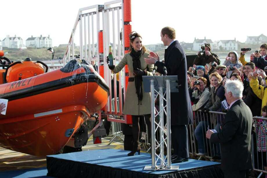 Britain's Prince William applaudes, as Kate Middleton holds uo a champagne bottle after naming a new lifeboat at the Trearddur Bay Lifeboat Station on the island of Anglesey, Wales, Thursday, Feb. 24, 2011. The visit had been highly anticipated because the couple have kept such a low profile since announcing their engagement in November, making only one other prior appearance at a charity event. They plan to marry April 29 at Westminster Abbey with just under 2,000 guests attending.(AP Photo/Jon Super). Photo: JON SUPER / AP