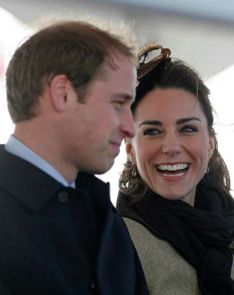 Britain's Prince William and his fiance Kate Middleton react following a naming ceremony and Service